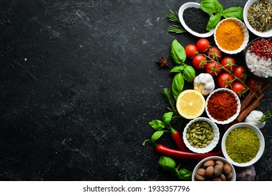 Set of Indian fragrant spices and herbs on a black stone background. Top view. Free space for text.