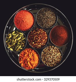 Set of indian spices in metal bowls - green cardamom, turmeric powder,  coriander seeds, cinnamon, cumin, and chili on black background