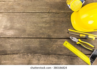 Set of industrial protective and work carpenter tools laid out on a rustic wooden table with copy space  including try square, screwdriver, pliers protective helmet, respirator and carpenter pencil.
