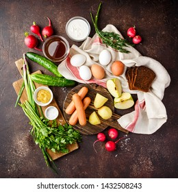 Set of ingredients for preparing traditional Russian cold soup Okroshka - boiled potatoes, sausages, radishes, boiled eggs, green onions, parsley, dill, sour cream, mustard, salt and kvass