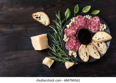 A set of Italian appetizers: salami and cheese, served with bread, olives, olive oil and wine decorated with napkin. Top View