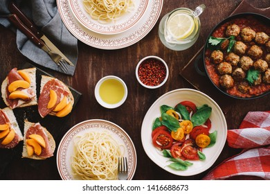 Set of Italian dishes. Tomato salad, spaghetti and meatballs with tomato sauce on  wooden table.
