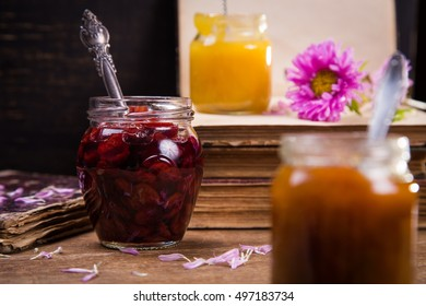 set of jam and honey in glass container with flower and book