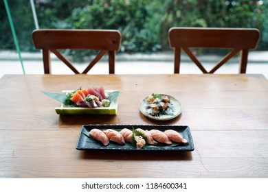 Set of Japanese food consist of Salmon sushi, Various sashimi (akami, aji, salmon) and Unagi sushi (grilled freshwater eel) on wooden table.