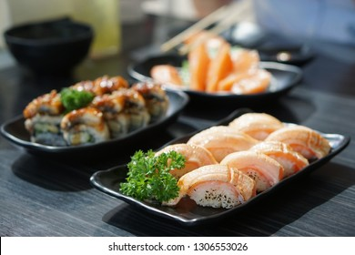 Set of Japanese food consist of Salmon sushi, Steamed rice topped with grilled eel (Unagi roll) and Fresh salmon sashimi on wooden table.