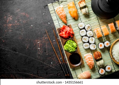 Set of Japanese sushi rolls with sauce and chopsticks. On dark rustic background