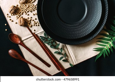 Set of japanese tableware. Black, white ceramic plates, brown bowls, wooden spoons and chopsticks on black background. Japanese serving style