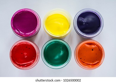 Set of jars of multicolored paint as background
