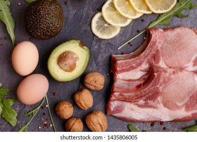 A set of keto diet products. Meat, walnuts, olive oil, chicken, avocado, lemon, greens and eggs