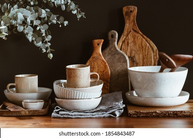 Set of kitchen ceramic tableware and wooden cutting boards on a table. Eco style home still life.