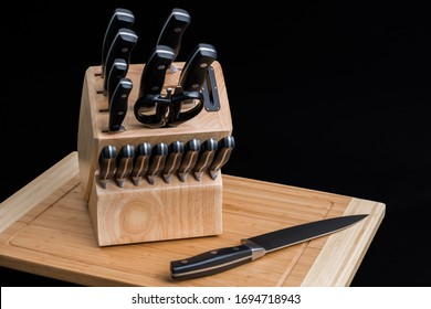 Set of Kitchen knives in a knife block with the chef knife laying on a cutting board, isolated on a black background