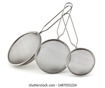 Set of kitchen strainers of different sizes on a white background. The smallest tea strainer and the largest for rice or pasta.