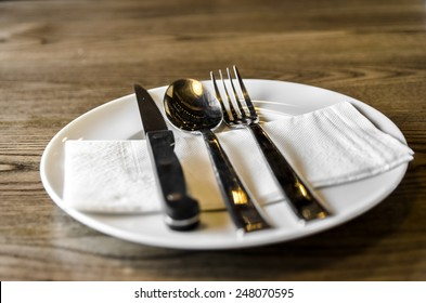 A set of knife, fork and spoon on wooden table