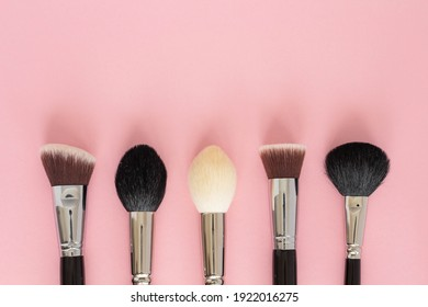 Set of large cosmetic brushes on pink background.