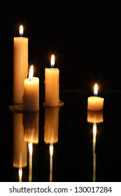 Set of lighting candles in a row on dark background with reverberation
