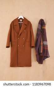 Set of long brown coat on hanging with scarf on wooden background