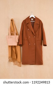 Set of long brown coat on hanging with scarf ,handbag on wooden background