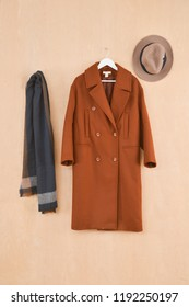 Set of long brown coat on hanging with scarf ,hat on wooden background