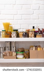 Set of long storage term foods on pantry shelf prepared for disaster emergency conditions on brick wall background