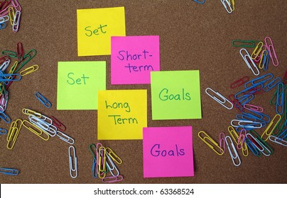 Set long term and short term goals written on post it notes on bulletin board with colorful paperclips