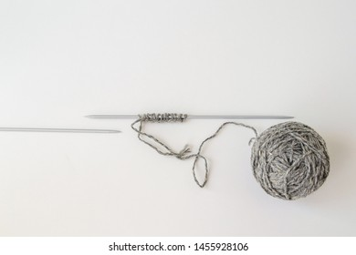 a set of loops on the knitting needle, hand knitting, wool yarn, grey ball and knitting needles,