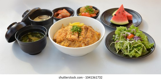 Set lunch pork fried rice with egg, soup, vegetable, fruit on black pottery plate, isolated on white background