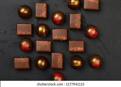 Set of luxury handmade bonbons on black background. Exclusive handcrafted chocolate candy. Product concept for chocolatier