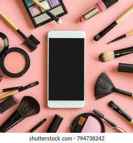 Set of make up brushes and cosmetics on pink background with smart phone and copy space