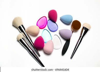 Set of makeup brushes, beauty blenders, silicone sponges and oval brush on a white background