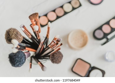 set of makeup brushes on the background of cosmetics, top view