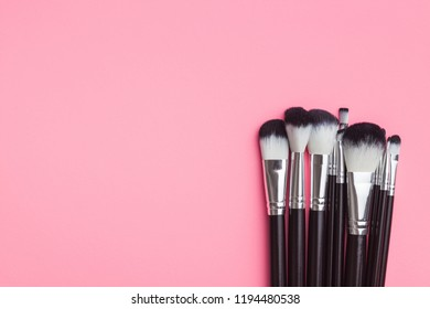 Set of makeup brushes on pink background. Flat lay.