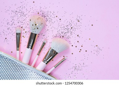 Set of makeup brushes on pink sparkling composed background. Top view point, flat lay.