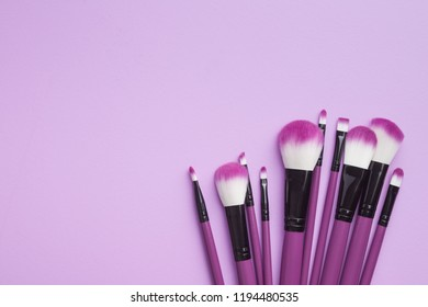 Set of makeup brushes on violet background. Flat lay.