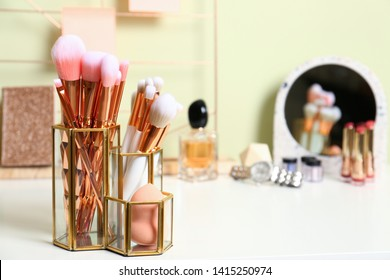 Set of makeup products and brushes on table. Space for text