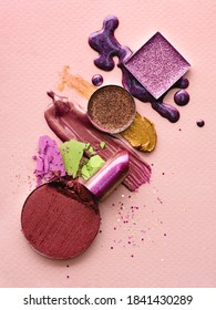 Set of makeup products on a pink background. Abstract composition of spilled and scattered makeup texture. Colourful beauty products for makeup artists or may be used as a design element.