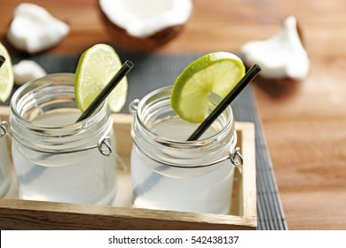 Set of mason jars with coconut water decorated with lime