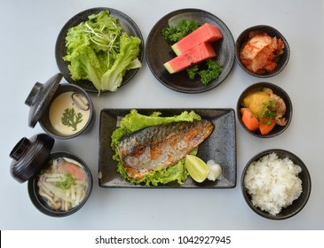 Set meal Japanese grilled saba fish on black pottery plate, isolated on white background