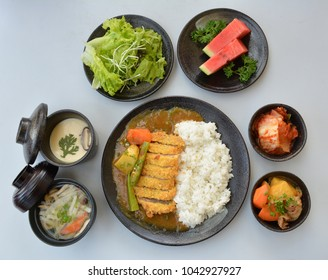 Set meal Japanese pork tempura rice on black pottery plate, isolated on white background