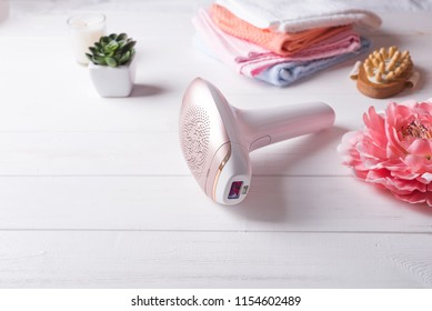 set of means of hair removal. Modern epilators in bathroom on a white wooden background.