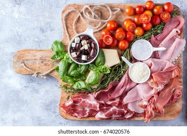 Set of meat antipasti served with herbs, cheese, tomatoes and olive oil on rustic wooden board over a stone background. Top view
