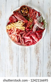 set of meat appetizer - jamon, chistorra, chorizo, salchichon, fuet, olives, rosemary, chili peppers on a white platter on a rustic wooden table, vertical view from above
