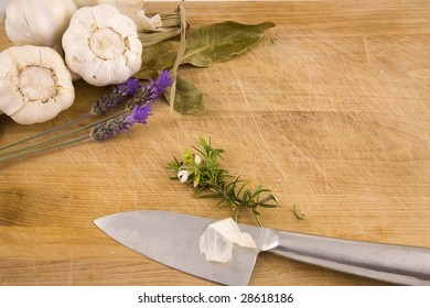 A set of Mediterranean ingredients over a wooden board ready to be chopped and used to flavor a meal