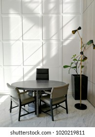 set of meeting table and chairs in from of sectioned wall hit by shadows created by sunlight from the window.
