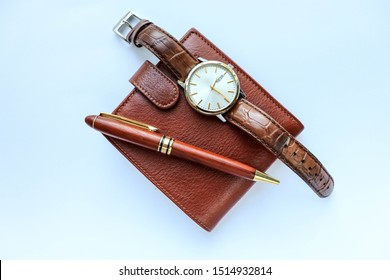 set of men's accessories. brown leather wallet, watch and pen on a white background