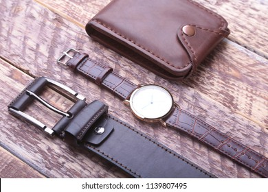 Set of men's accessories for the business with leather belt, wallet, watch and smoking pipe on a wooden background. The concept of fashion and travel.