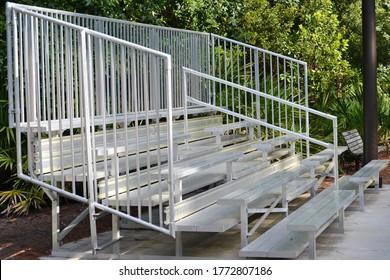 A set of metal bleachers in an empty baseball field