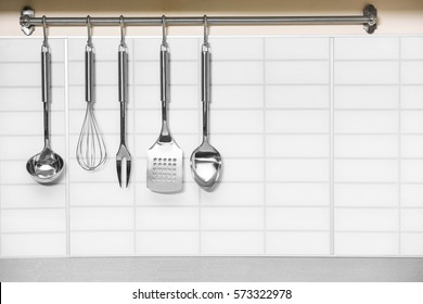 Set of metal kitchen utensils hanging on wall