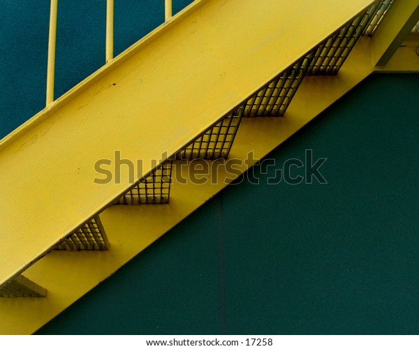 A set of metal stairs detail against a green wall