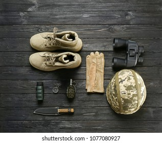 Set of military equipment and combat boots on wooden background, flat lay