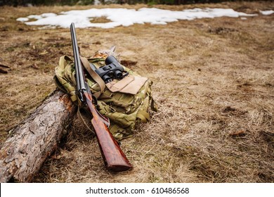 Set of military hunting equipment with rifle in forest during hunting season. Bushcraft, hunting and gun concept